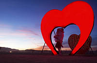 People kissing under Red Heart Burning Man installation