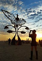 Woman taking a picture of metal butterfly wings art sculpture