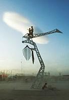 People climbing the crane art sculpture