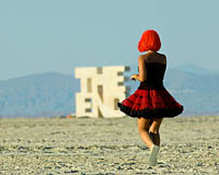 Burning Man Girl dancing next to the End sign