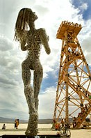 Sculpture of woman looking up the oil tower
