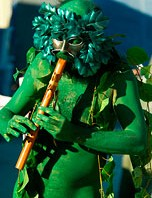 Green painted man playing his flute