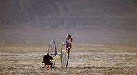 women playing on teeter totter in desert