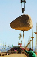 Man pulling one of the suspended Colossus stones