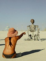 Woman pointing finger at human sized metal skeleton sculpture