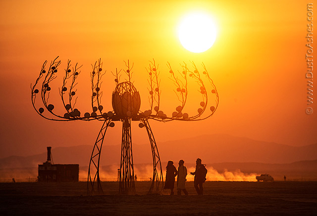 Silhouettes of Burning Man people in the morning sunrise